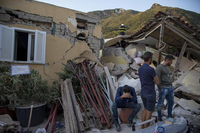 <p>A man sits on a bucket as others look on near a wracked building after 4.0-magnitude richter scale earthquake hit Ischia Island's Casamicciola Terme of Naples, Italy on Aug. 22, 2017. (Photo: Alessio Paduano/Anadolu Agency/Getty Images) </p>