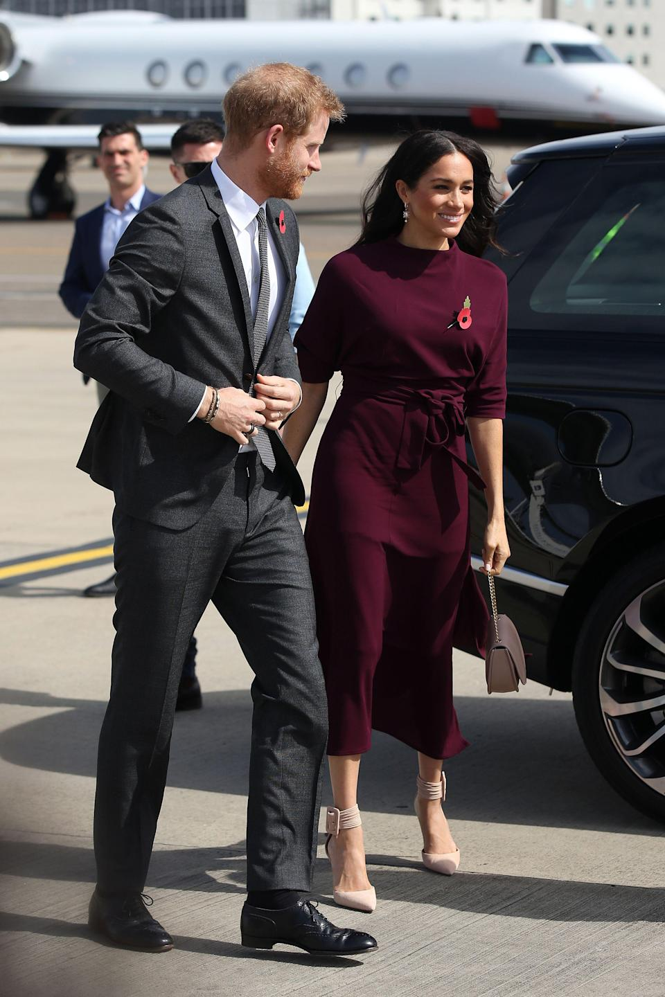 "<p>Ever the chic traveller, Meghan wore a £249 Hugo Boss <a href=""https://www.hugoboss.com/uk/slim-fit-dress-in-soft-jersey-with-detachable-belt/4029049659730.html?gclid=CjwKCAjwmdDeBRA8EiwAXlarFkvy4fNgIW0KHOqep_etwdTAUvkw4z7IOyxiqkgag1-uXxTHOsF5XBoCsnkQAvD_BwE&awc=3767_1540828613_576abe11bbac8135e80a0ee53d87aeac&utm_source=affiliatewindow&utm_medium=affiliate&utm_term=136348&utm_content=home&utm_campaign=season"" rel=""nofollow noopener"" target=""_blank"" data-ylk=""slk:dress"" class=""link rapid-noclick-resp"">dress</a> in a winter-ready berry hue for their departure from Sydney airport. <em>[Photo: Getty]</em> </p>"