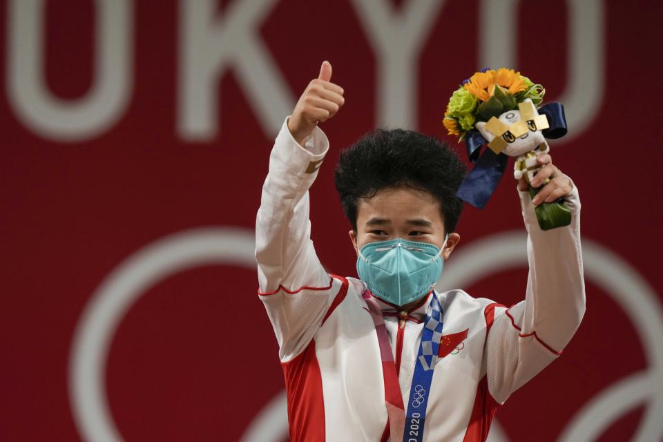 Hou Zhihui of China celebrates on the podium after winning the gold medal in the women's 49kg weightlifting event, at the 2020 Summer Olympics, Saturday, July 24, 2021, in Tokyo, Japan. (AP Photo/Luca Bruno)