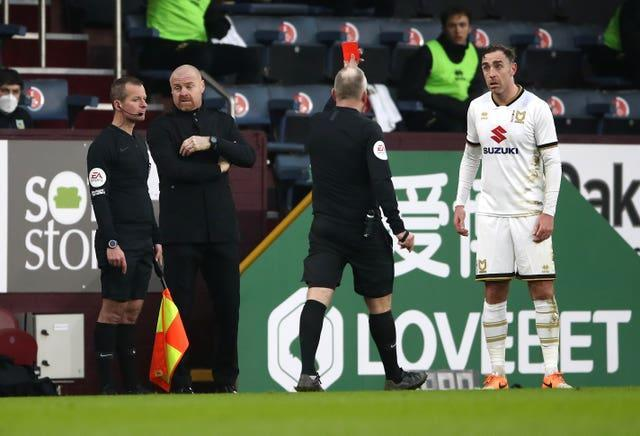 Referee Jon Moss, centre, shows a red card to Richard Keogh, right, before overturning the decision on review