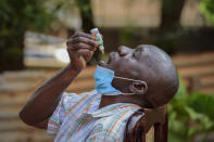 """FILE - In this Tuesday, July 6, 2021 file photo, a man with a cough but who had not been tested for the coronavirus uses """"COVIDEX,"""" a locally-made herbal medicine approved by the government for use as a supportive treatment for viral infections, in Kampala, Uganda. Some hospitals with COVID-19 wards are charging prohibitive sums for most Ugandans and many are self-medicating within their homes, experimenting with everything from traditional medicine to a newly approved herbal remedy selling briskly as COVIDEX. (AP Photo/Nicholas Bamulanzeki)"""