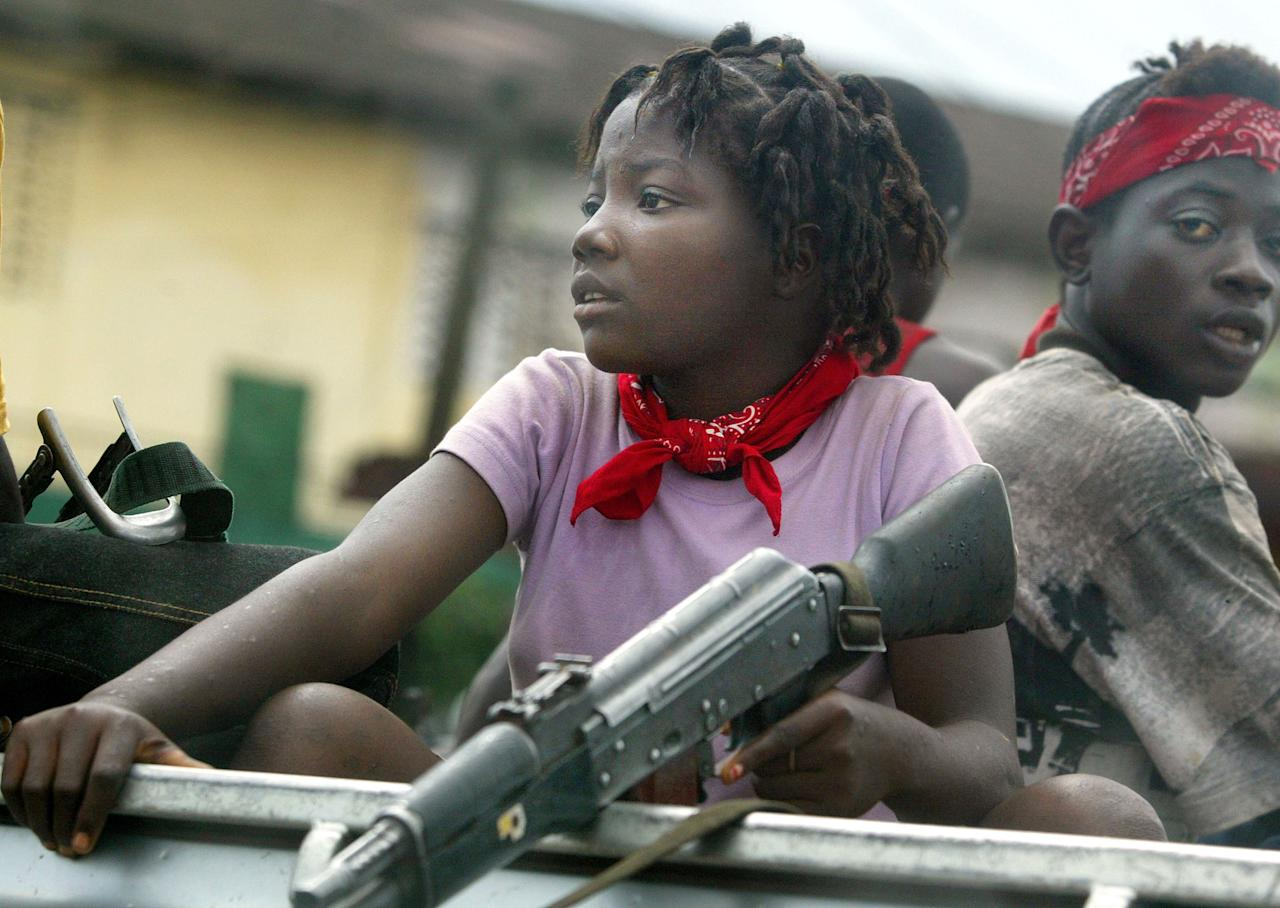 <p>A young female soldier sits in a truck just prior to a rebel attack July 19, 2003 near front line positions just outside Monrovia, Liberia. In an unexpected move, rebels attacked the capital this afternoon. (Photo by Chris Hondros/Getty Images) </p>