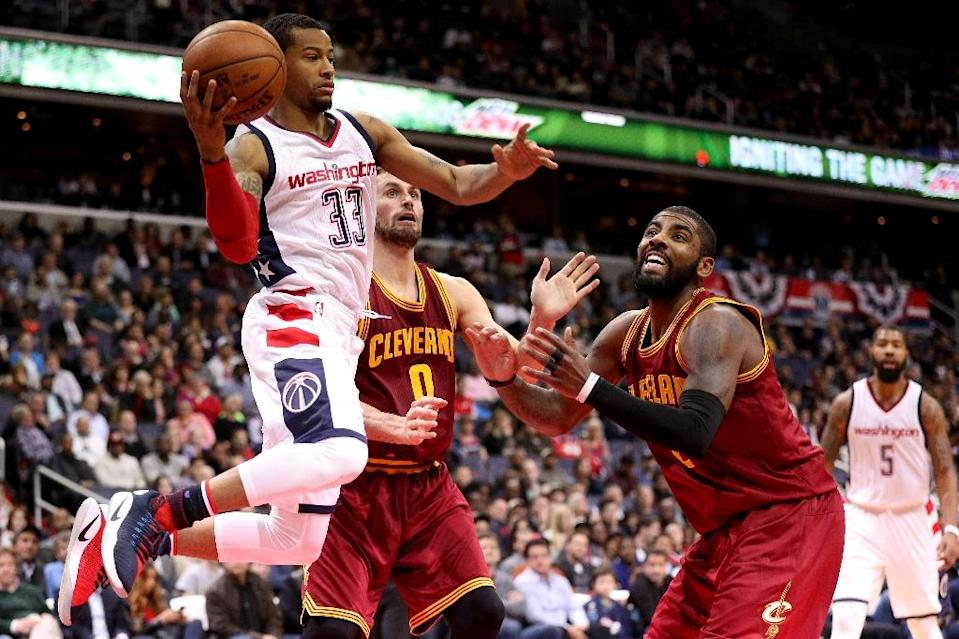 Trey Burke of the Washington Wizards looks to make a pass in front of Kyrie Irving (R) of the Cleveland Cavaliers at Verizon Center (AFP Photo/Patrick Smith)