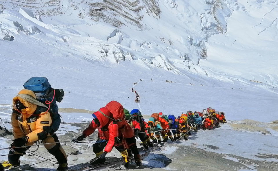 FILE - In this May 22, 2019, file photo, a long queue of mountain climbers line a path on Mount Everest just below camp four, in Nepal. Expedition operators on Mount Everest say that Chinese mountaineering officials will not allow spring climbs from their side of the mountain due to fears of the coronavirus. (AP Photo/Rizza Alee, File)
