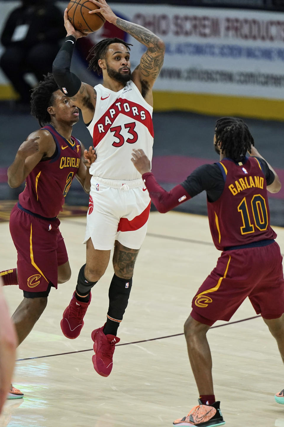 Toronto Raptors' Gary Trent Jr. (33) looks to pass against Cleveland Cavaliers' Collin Sexton (2) and Darius Garland (10) in the second half of an NBA basketball game, Saturday, April 10, 2021, in Cleveland. (AP Photo/Tony Dejak)
