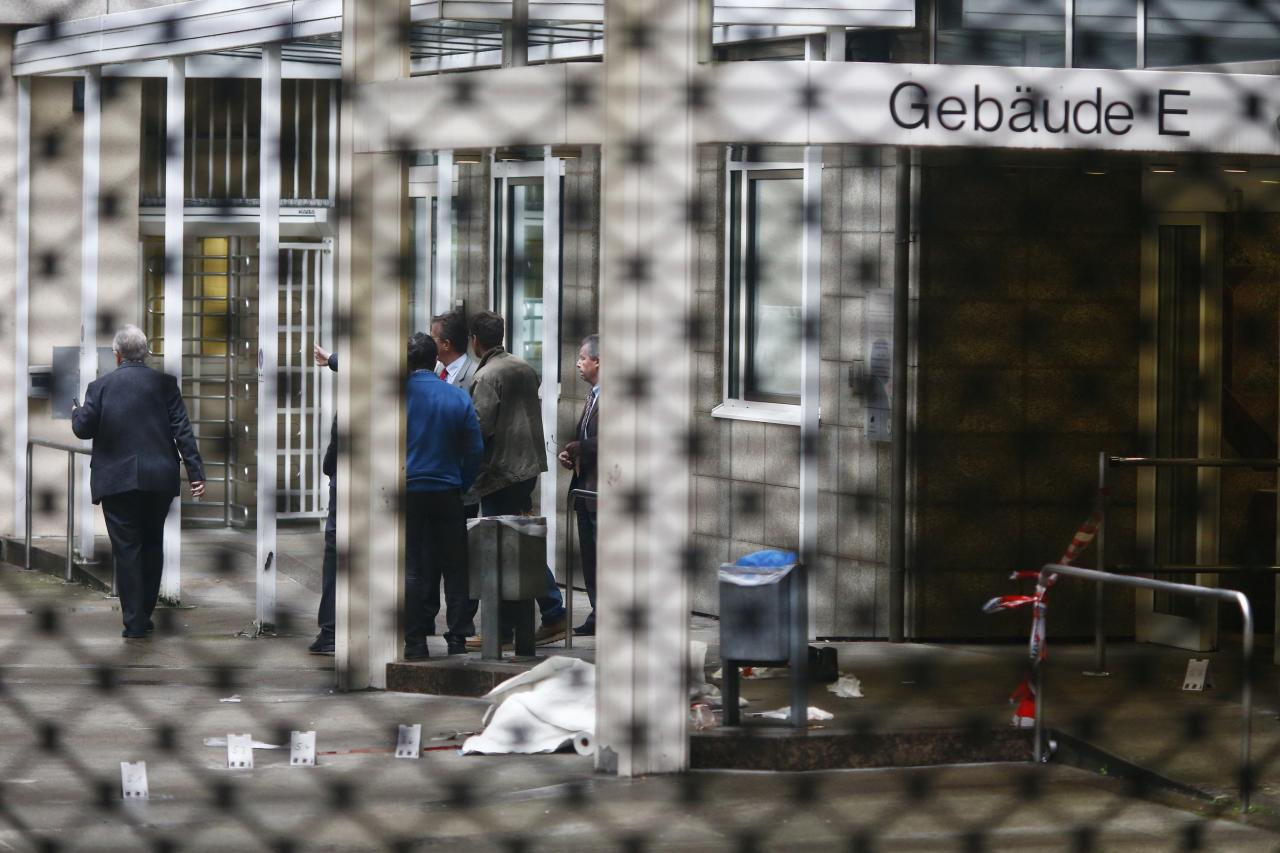 A covered body lies on the ground at the crime scene following a shooting at the entrance of Building E of the courthouse in Frankfurt January 24, 2014. REUTERS/Ralph Orlowski (GERMANY - Tags: CRIME LAW)
