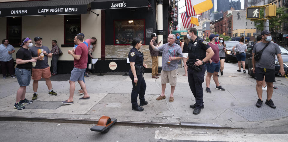 Police officers on patrol check on a small crowd outside a bar in the Hell's Kitchen neighborhood of New York, Friday, May 29, 2020, during the coronavirus pandemic. The street has been blocked off from traffic to allow residents to gather in open spaces with some social distancing. (AP Photo/Mark Lennihan)