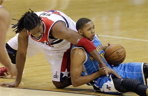 Washington Wizards center Nene (42), from Brazil, and New Orleans Hornets guard Eric Gordon (10) scramble for the loose ball in the second half of an NBA basketball game Friday, March 15, 2013 in Washington. The Wizards won 96-87. (AP Photo/Alex Brandon)