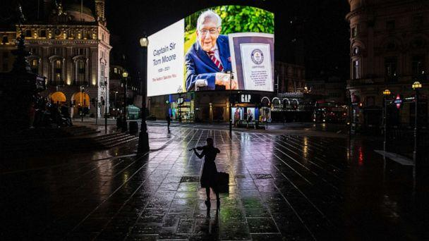 PHOTO: A violinist plays in front of a tribute to Captain Sir Tom Moore that is displayed at Piccadilly Circus shortly after it was announced that he has died on Feb. 2, 2021 in London. (Chris J Ratcliffe/Getty Images)