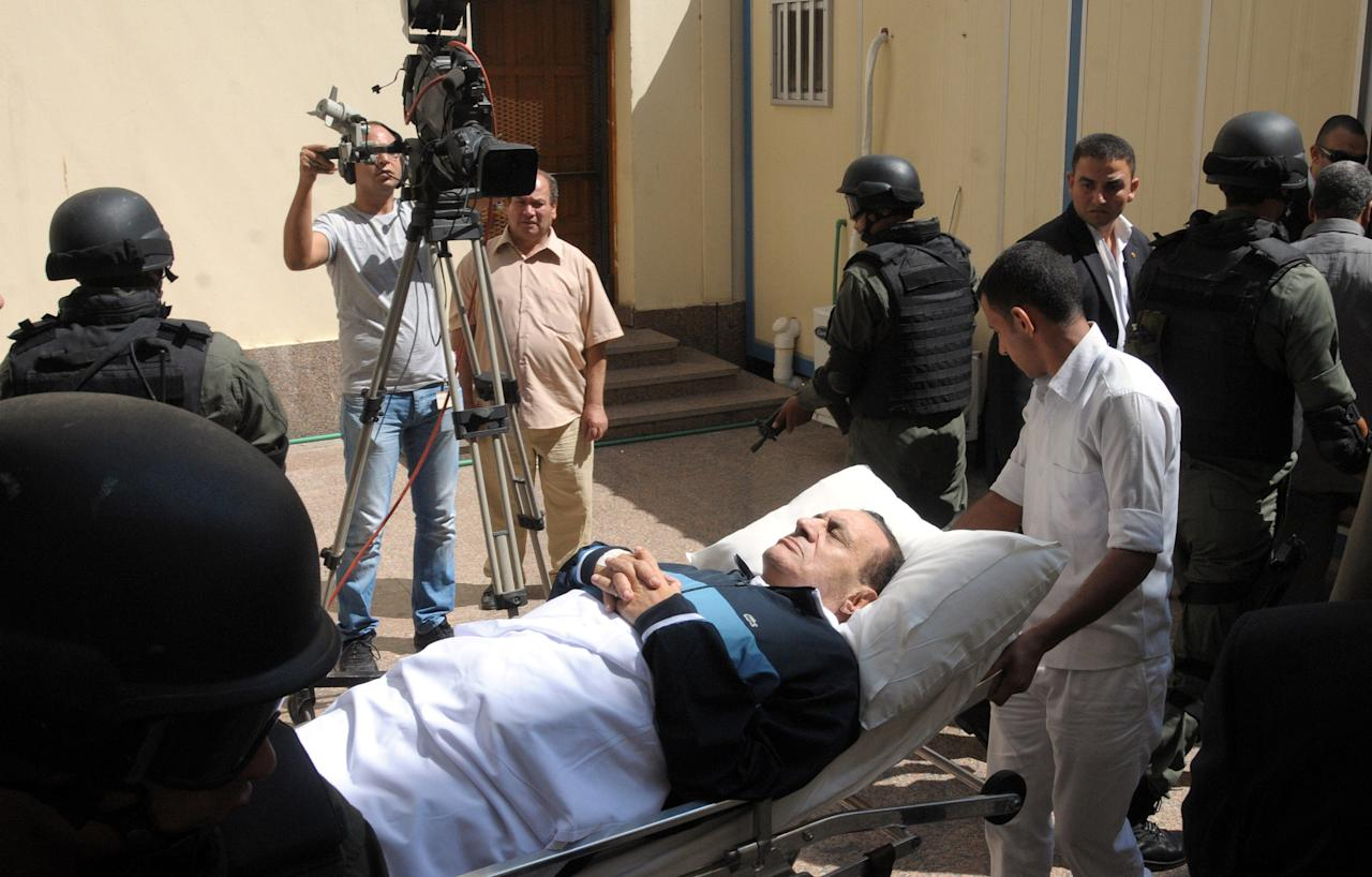 FILE - In this Sept. 7, 2011 file photo, former Egyptian president Hosni Mubarak lies on his bed while being taken to the courtroom for another session of his trial in Cairo, Egypt. An Egyptian prison official says Hosni Mubarak's health has taken a turn to the worst and is likely to be moved out of his prison hospital to a military facility nearby. The official said Tuesday doctors reported that the 84-year old former president has fallen unconscious. He said they have used a defibrillator to restart his heart, and have been administering breathing aid. (AP Photo/Mohammed al-Law, File)