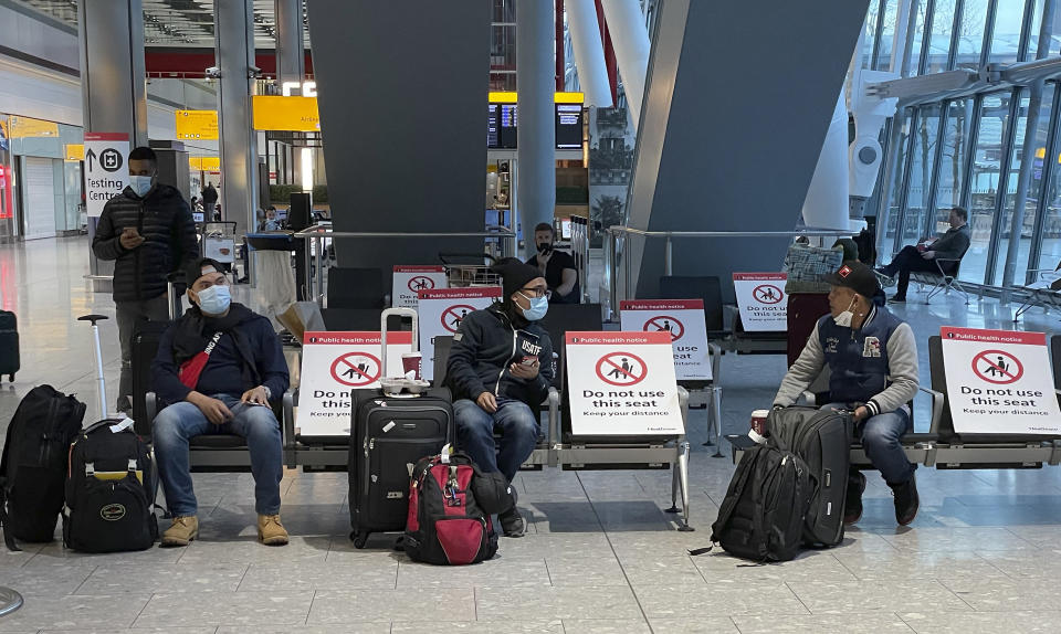 Travellers wait for their Covid-19 test results at Heathrow Airport in London, Sunday, Jan. 17, 2021. The UK will close all travel corridors from Monday morning to protect against the coronavirus, with all travellers to have a negative COVID-19 test to enter the country. (AP Photo/Frank Augstein)