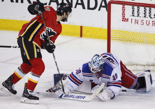 New York Rangers goalie Henrik Lundqvist, right, of Sweden, makes a save against Calgary Flames' Michael Frolik, of the Czech Republic, during second-period NHL hockey game action in Calgary, Alberta, Friday, March 2, 2018. (Larry MacDougal/The Canadian Press via AP)