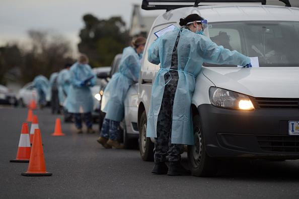 Members of the Australian Defence Force (ADF) gather information and conduct temperature checks at a drive-in Covid-19 testing site set up at the Melbourne Show Grounds in Melbourne.
