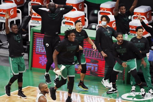 The Boston Celtics bench celebrates after the go-ahead basket by Jaylen Brown with less than a second left on the clock during the second half of an NBA basketball game against the Milwaukee Bucks, Wednesday, Dec. 23, 2020, in Boston. (AP Photo/Michael Dwyer)