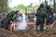 FILE - In this May 15, 2020, file photo, cemetery workers in protective suits disinfect a grave as they bury a COVID-19 victim in a section of the Butovskoye cemetery reserved for coronavirus victims outside Moscow, Russia. Coronavirus deaths in Russia hit a record on Friday, Oct. 1, 2021 for the fourth straight day, and confirmed cases continued to surge as well. Russia's state coronavirus task force reported 887 deaths, the country's highest daily number in the pandemic. The previous record, from a day earlier, stood at 867. (Kirill Zykov, Moscow News Agency photo via AP, File)