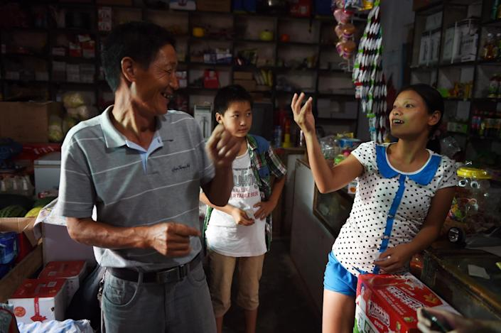 Vietnamese bride Vu Thi Hong Thuy chats with Chinese customers in the shop where her friend, also Vietnamese, works in Weijian village, China's Henan province on July 29, 2014 (AFP Photo/Greg Baker)