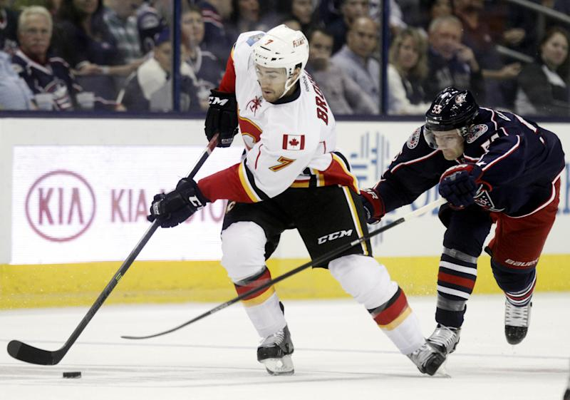 Calgary Flames' T.J Brodie (7) works for the puck against Columbus Blue Jackets' Mark Letestu in the first period of an NHL hockey game in Columbus, Ohio, Friday, Oct. 4, 2013. (AP Photo/Paul Vernon)