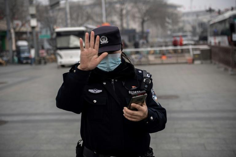 A police officer gestures to a photojournalist not to take photos outside China's parliament
