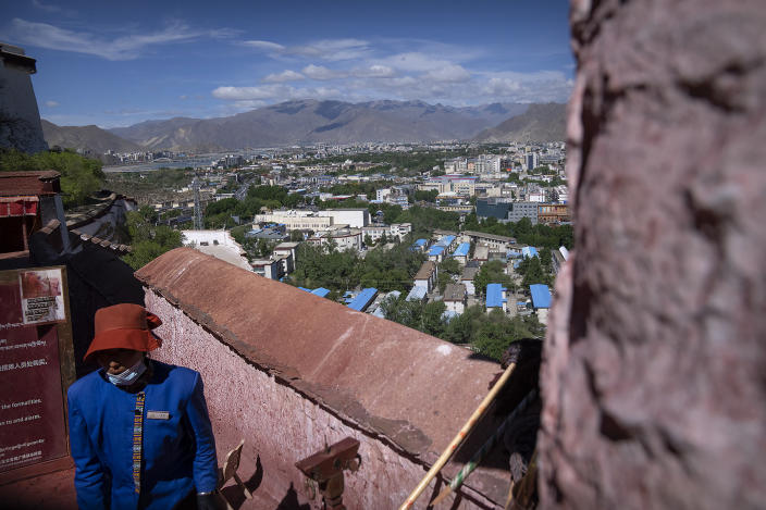 A staff member stands on a rampart at the Potala Palace overlooking the modern city skyline of Lhasa in western China's Tibet Autonomous Region, as seen during a rare government-led tour of the region for foreign journalists, Tuesday, June 1, 2021. Long defined by its Buddhist culture, Tibet is facing a push for assimilation and political orthodoxy under China's ruling Communist Party. (AP Photo/Mark Schiefelbein)