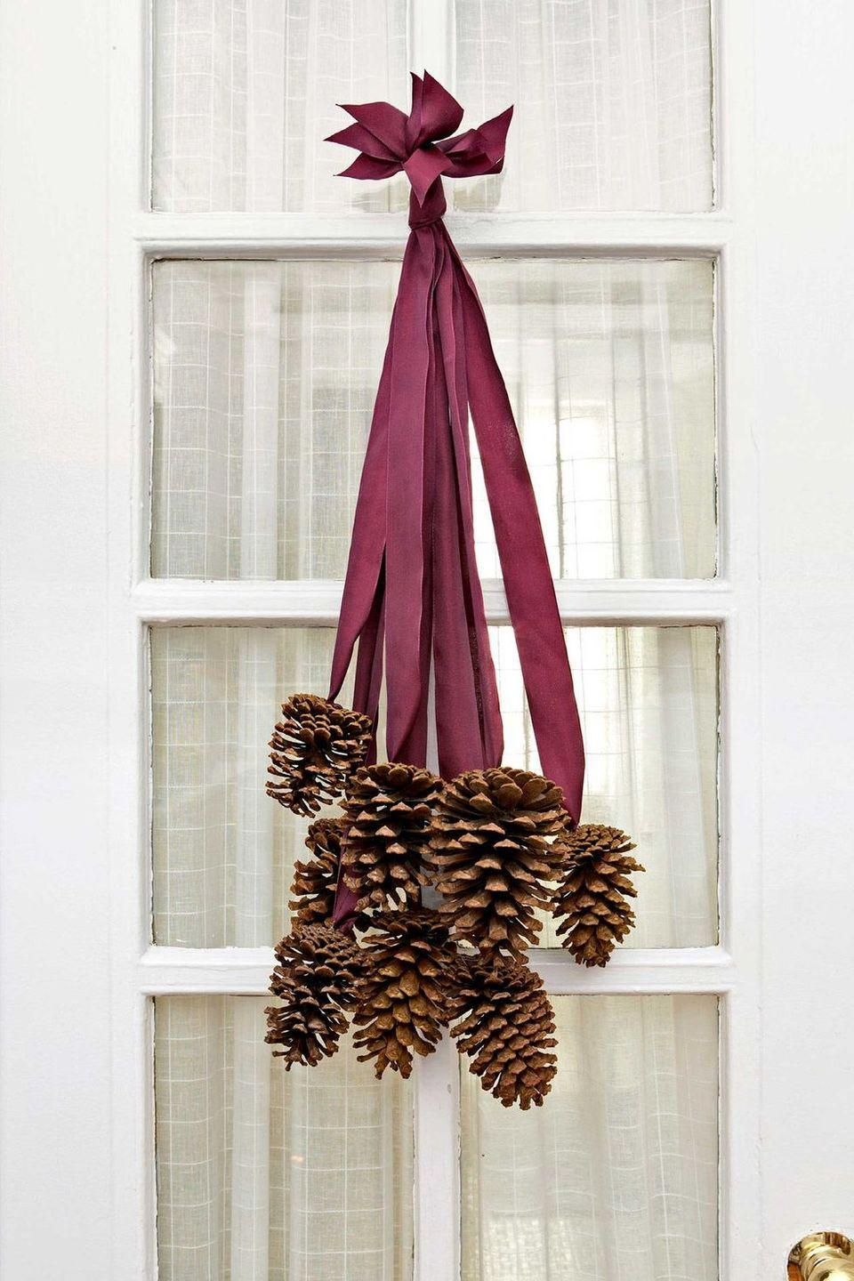 <p>Not all DIY front-door decor requires a foam wreath form. Choose a ribbon color that coordinates with the rest of your decor.<br></p><p><strong>Make the hanger: </strong>Select 8 four- to six-inch pinecones and 8 two-foot-long pieces of silk ribbon. Use a hot-glue gun to adhere the last two inches of each ribbon to the base of a cone. After the glue dries, collect all the ribbon ends and stagger them so that the cones fall at varying lengths. Tie the ribbon ends together in a knot, trim the tips so they are uniform, and slip the knot over a finishing nail. </p>