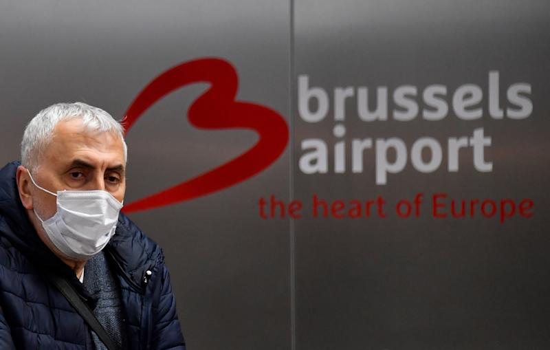 A passenger wearing a protective facemask arrives at the Brussels Airport, in Zaventem, outside Brussels, on March 9, 2020, during a COVID-19 outbreak. - All European Union States are hit by the novel coronavirus. (Photo by JOHN THYS / AFP) (Photo by JOHN THYS/AFP via Getty Images)