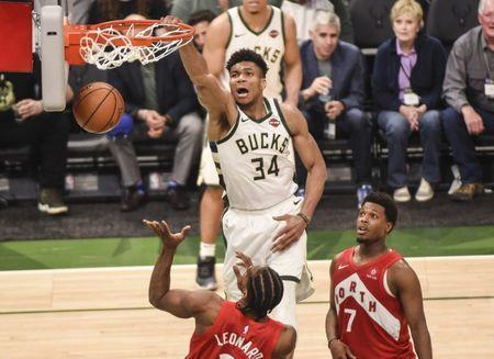 May 23, 2019; Milwaukee, WI, USA; Milwaukee Bucks forward Giannis Antetokounmpo (34) dunks the ball past Toronto Raptors forward Kawhi Leonard (2) and guard Kyle Lowry (7) in the third quarter in game five of the Eastern conference finals of the 2019 NBA Playoffs at Fiserv Forum. Mandatory Credit: Benny Sieu-USA TODAY Sports