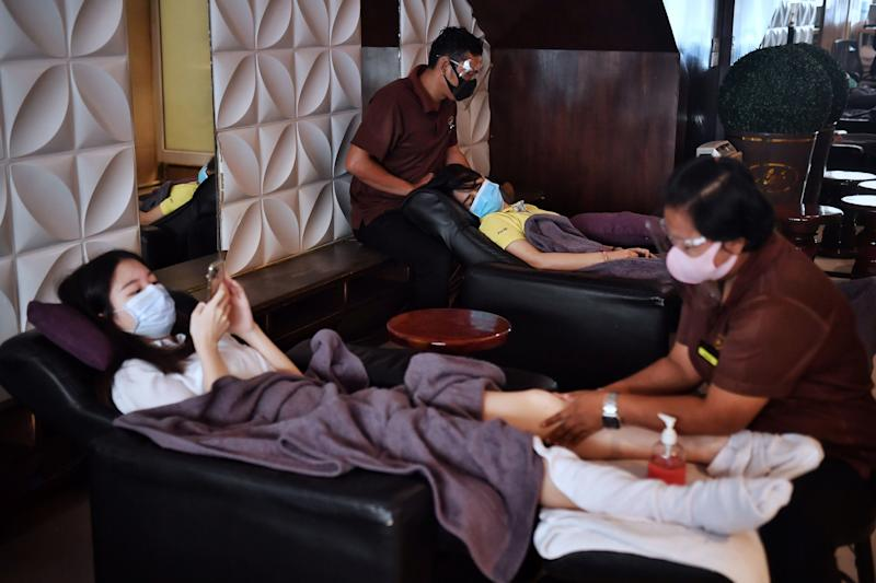 FILE PHOTO: A masseuse attends to a customer as massage parlors reopen in Bangkok on June 1, 2020 for the first time in more than two months after authorities lifted some coronavirus restrictions. (Photo by LILLIAN SUWANRUMPHA/AFP via Getty Images)