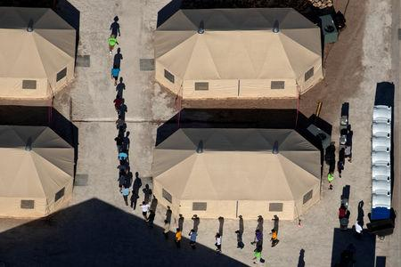 FILE PHOTO: Immigrant children are led by staff in single file between tents at a detention facility in Tornillo, Texas