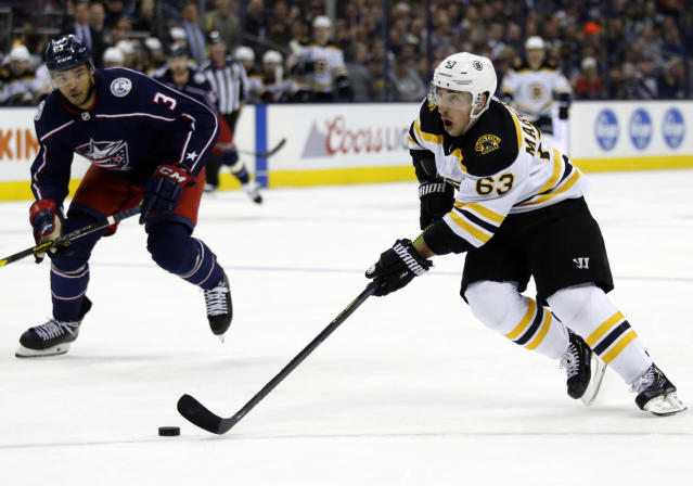 Boston Bruins forward Brad Marchand, right, controls the puck in front of Columbus Blue Jackets defenseman Seth Jones during the first period of an NHL hockey game in Columbus, Ohio, Tuesday, April 2, 2019. (AP Photo/Paul Vernon)