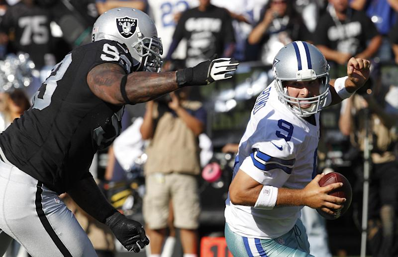 Oakland Raiders defensive tackle Tommy Kelly (93) sacks Dallas Cowboys quarterback Tony Romo (9) during the first quarter of an NFL preseason football game in Oakland, Calif., Monday, Aug. 13, 2012. (AP Photo/Tony Avelar)