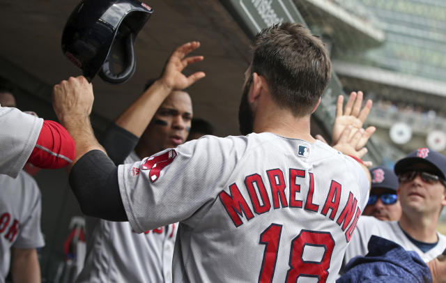 Boston Red Sox' s Mitch Moreland is greeted in the dugout after scoring on a Xander Bogaerts hit off Minnesota Twins pitcher Kyle Gibson in the fourth inning of a baseball game Thursday, June 21, 2018, in Minneapolis. (AP Photo/Jim Mone)