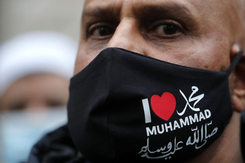 A protester wearing a face mask outside the French embassy in London, Friday, Oct. 30, 2020, to protest against French President Macron. Protesters are upset over the publication of pictures and what they see as disrespect of the Prophet Muhammad, in the wake of the terror attack in Nice, France. (AP Photo/Frank Augstein)