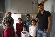 Abdul Salam Al Khawien, 37, right, and his wife Kariman, 32, left, pose with their children for a family photo, at their apartment in the northern city of Thessaloniki, Greece, Saturday, May 1, 2021. Sundered in the deadly chaos of an air raid, a Syrian family of seven has been reunited, against the odds, three years later at a refugee shelter in Greece's second city of Thessaloniki. (AP Photo/Giannis Papanikos)