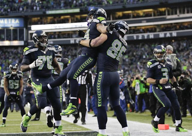 Seattle Seahawks running back Marshawn Lynch (24) celebrates with tight end Zach Miller (86) after running for a 31-yard touchdown against the New Orleans Saints during the fourth quarter of an NFC divisional playoff NFL football game in Seattle, Saturday, Jan. 11, 2014. (AP Photo/John Froschauer)
