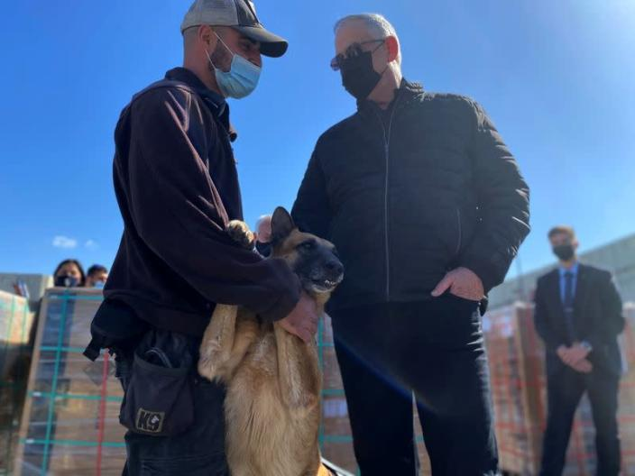 Israeli Defence Minister Benny Gantz stands next to a sniffer dog and cargo headed for the Gaza Strip during a tour of the Gaza border area, at the Kerem Shalom crossing in southern Israel