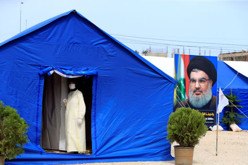 A medic wearing protective gear stands inside a tent facility in al-Ghaziyeh