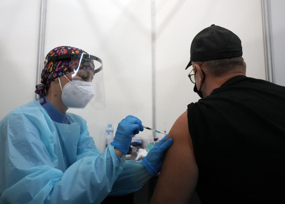 A medical worker administers a shot of Pfizer COVID-19 vaccine to Vitaly Pavlov from Rostov-on-Don at Belgrade Fair makeshift vaccination center in Belgrade, Serbia, Saturday, Oct. 2, 2021. Pavlov looked for a vaccine that would allow his family to travel freely — a quest that brought them to Serbia, where hundreds of Russian citizens have flocked in recent weeks to receive Western-approved COVID-19 shots. (AP Photo/Darko Vojinovic)