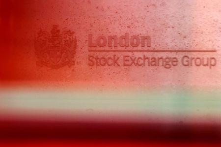 A red London bus passes the Stock Exchange in London