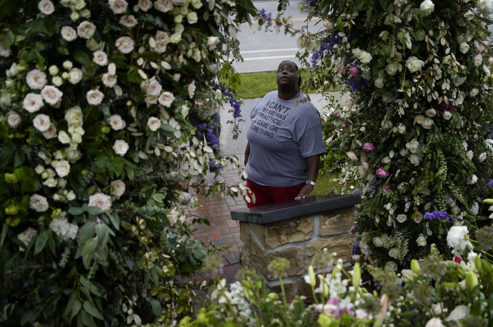 Raekeisha Watkins visits flowers left as a memorial for the Tulsa Race Massacre near the historic greenwood district during centennial commemorations of the massacre, Monday, May 31, 2021, in Tulsa, Okla. (AP Photo/John Locher)
