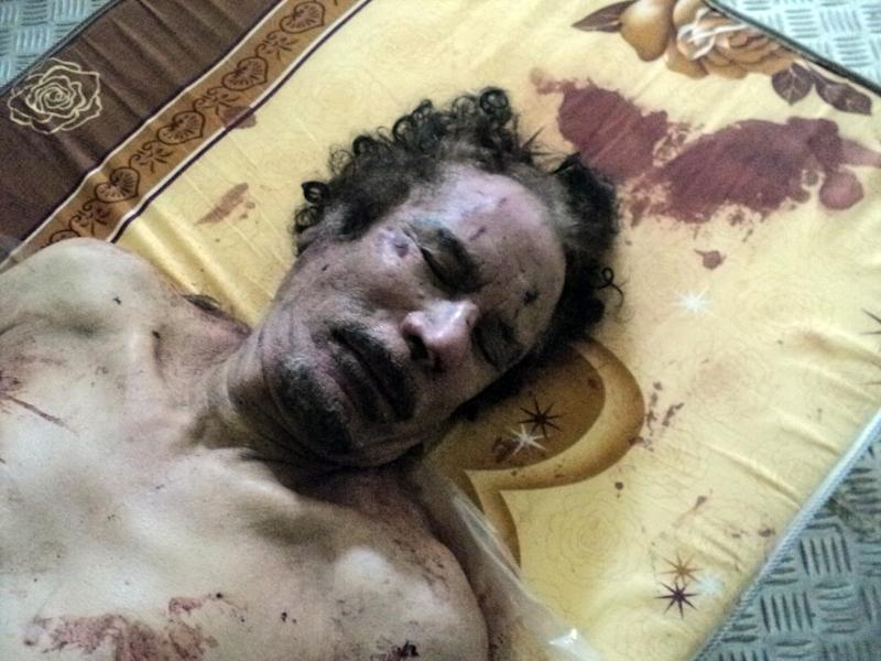 The body of Libyan dictator Moammar Gadhafi lies on a mattress in a commercial freezer at a shopping center  Misrata, Libya, Friday, Oct. 21, 2011. The burial of slain leader Moammar Gadhafi has been delayed until the circumstances of his death can be further examined and a decision is made about where to bury the body, Libyan officials said Friday, as the U.N. human rights office called for an investigation into his death. (AP Photo/Rami al-Shabheibi)