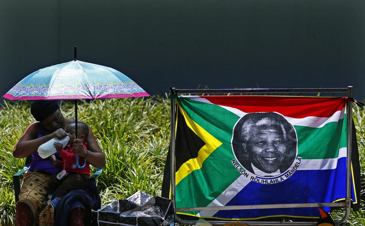 A woman gives water to her baby while sitting the house of former South African President Nelson Mandela in Johannesburg