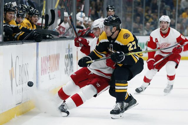 Boston Bruins' John Moore (27) battles Detroit Red Wings' Dylan Larkin, center left, for the puck during the first period of an NHL hockey game in Boston, Saturday, Dec. 1, 2018. (AP Photo/Michael Dwyer)