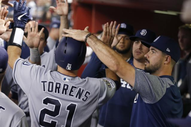 San Diego Padres' Luis Torrens (21) celebrates his run scored against the Arizona Diamondbacks with teammates, including Joey Lucchesi, right, during the seventh inning of a baseball game Friday, Sept. 27, 2019, in Phoenix. (AP Photo/Ross D. Franklin)