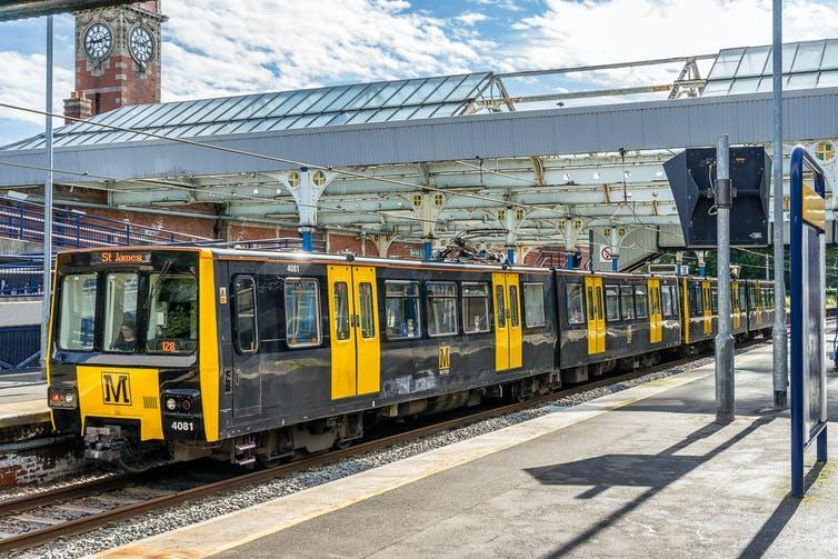 Yellow and black light rail train in station.