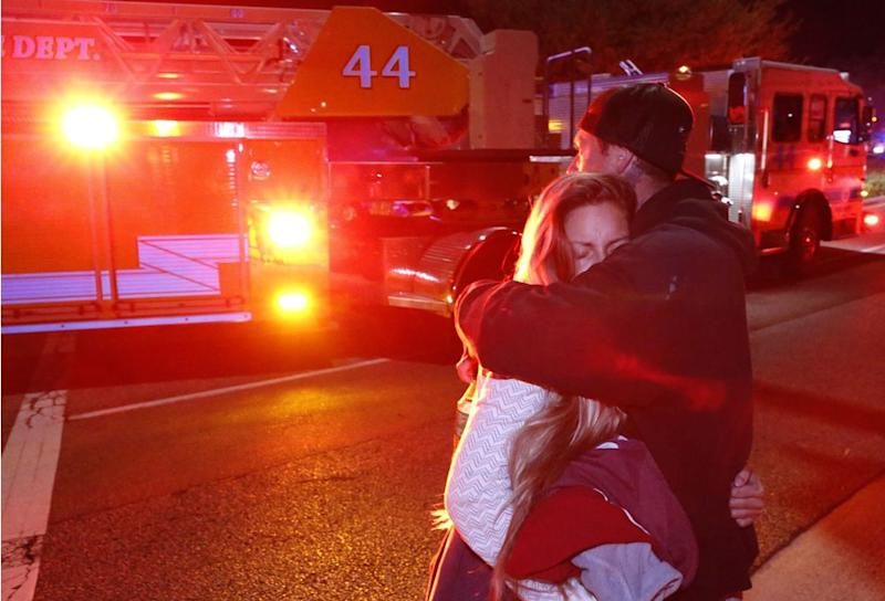 Families embrace at the scene of the Borderline Shooting