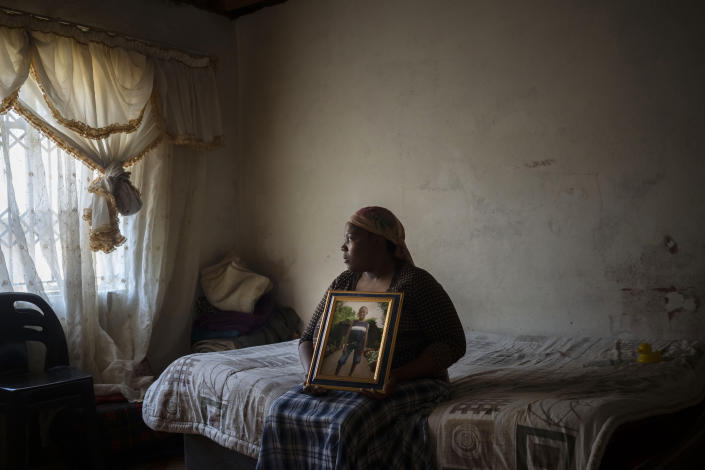 Rebecca Mohapi poses with a photograph in the bedroom of her son, 12-year-old Onthatile Mohapi, who mysteriously disappeared and was found dead a week later in Damonsville, South Africa, on June 8, 2020. The police report said the boy drowned, but his mother believes he was murdered. (AP Photo/Bram Janssen)