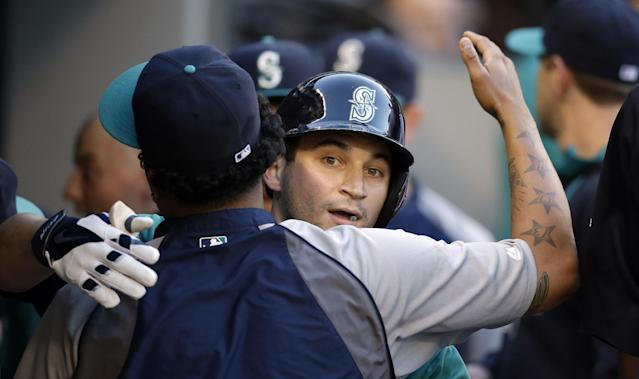 Seattle Mariners' Mike Zunino, right, is embraced by Felix Hernandez in the dugout after Zunino's home run against the Minnesota Twins in the second inning of a baseball game Monday, July 7, 2014, in Seattle. (AP Photo/Elaine Thompson)