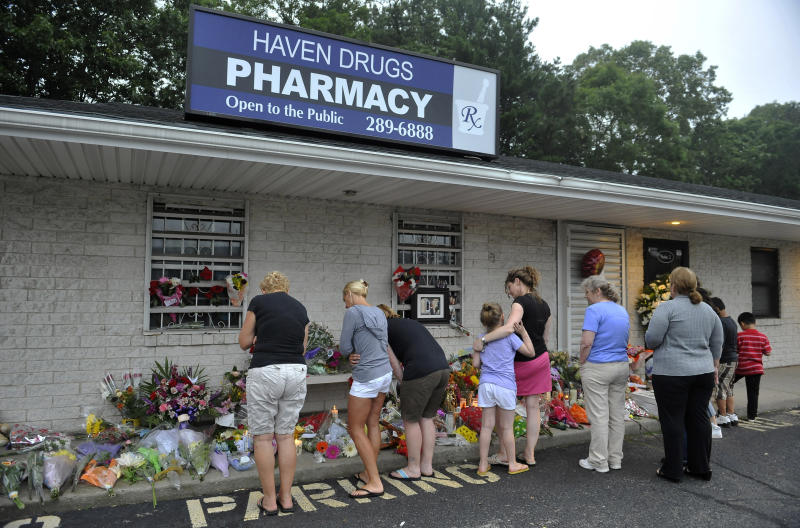 FILE In this file photo of June 22, 2011, people bring flowers to Haven Drugs pharmacy where four people were shot and killed during a botched weekend painkiller robbery in Medford, N.Y. A wave of pharmacy robberies is sweeping across the United States as desperate addicts and ruthless dealers turn to violence to feed the nation's growing hunger for narcotic painkillers.  (AP Photo/Kathy Kmonicek, File)