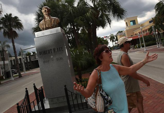 <p>Jacki Lewan and Steve Lewan (L-R), from Pittsburgh, Pennsylvania, walk away after looking at a bronze bust of Confederate general Robert E. Lee on display in the median on Monroe street in the midst of a national controversy over whether Confederate symbols should be removed from public display on August 18, 2017 in Fort Myers, Fla. (Photo: Joe Raedle/Getty Images) </p>