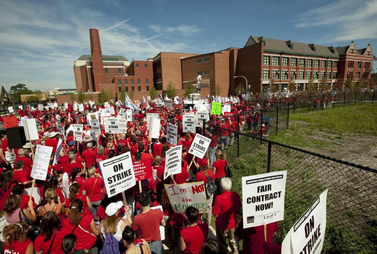 A large group of public school teachers marches past John Marshall Metropolitan High School on Wednesday, Sept. 12, 2012 in West Chicago. Teachers walked off the job Monday for the first time in 25 years over issues that include pay raises, classroom conditions, job security and teacher evaluations. (AP Photo/Sitthixay Ditthavong)